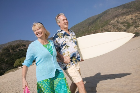 Couple with surfboard smiling on beach Stock Photo - 8822724