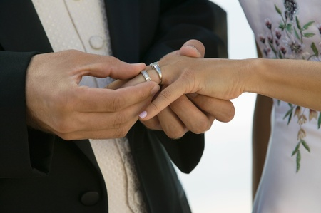 ring stand: Groom placing ring on brides finger (close-up)