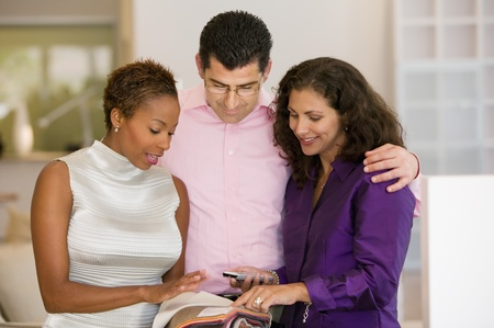 Saleswoman and Couple Examining Fabric Swatches in furniture store front view Stock Photo - 8822744