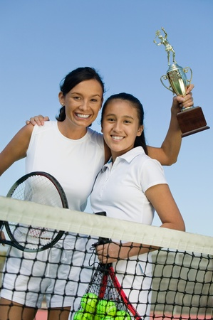 Mother and daughter standing at net on tennis court holding trophy portrait low angle view Stock Photo - 8822755