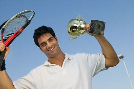 Male Tennis Player raising tennis rackets and Trophy portrait Stock Photo - 8822780
