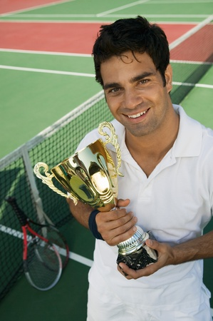 Male Tennis Player standing on tennis court holding trophy portrait high angle view Stock Photo - 8822781