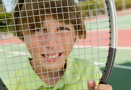 pre teen boys: Boy Looking Through Tennis Racket portrait close up