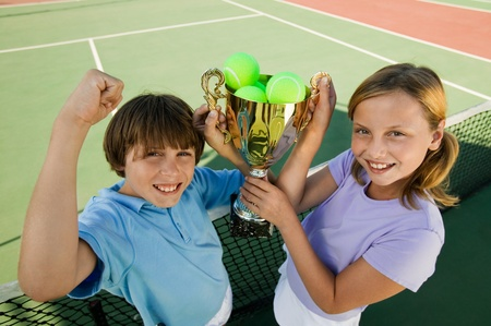pre adolescent boys: Brother and Sister on tennis court holding up Trophy portrait high angle view LANG_EVOIMAGES