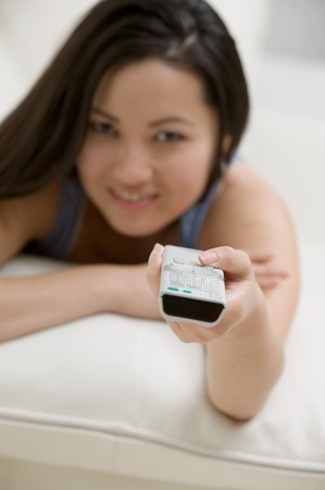 personal perspective: Young Woman lying on Couch using Remote Control personal perspective focus on remote control