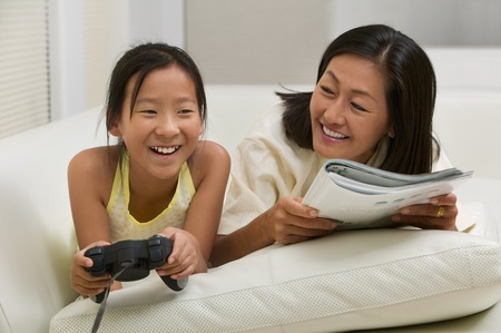 Mother reading on couch with Daughter Playing Video Game front view Stock Photo - 8822826