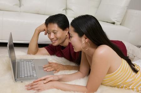 Couple lying on Rug with Laptop Stock Photo - 8822841