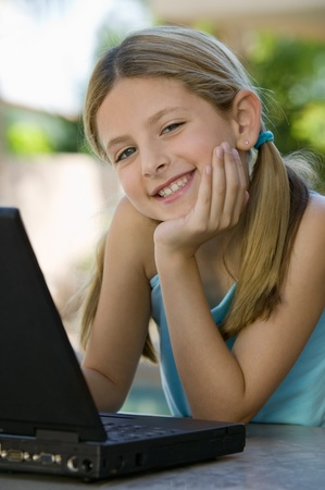 child girl: Girl Using Laptop on Patio