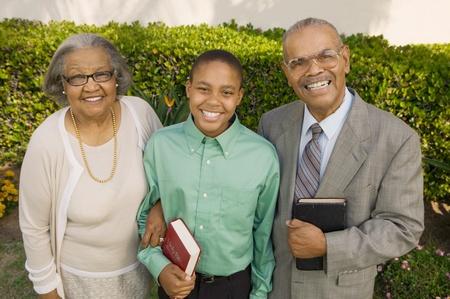 familia en la iglesia: Abuelos cristianos y nieto en el jard�n con retrato de Biblias
