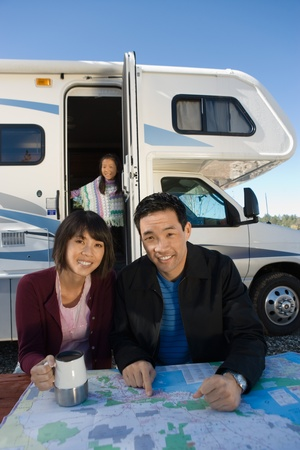 Couple with daughter looking at map on picnic table outside RV Stock Photo - 8822887