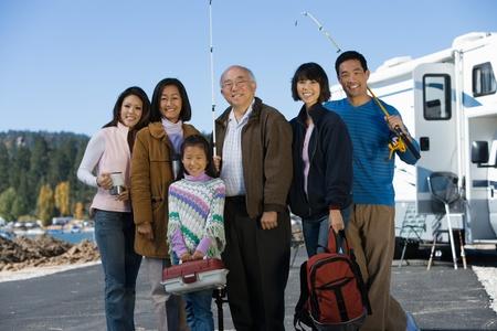 asian travel: Three-generation family holding fishing poles by RV at lake