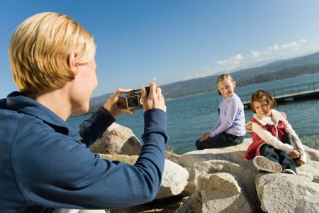 Mother taking picture of daughters at the lake Stock Photo - 8836124
