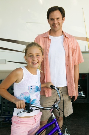 pre adult: Father with Daughter on Bike Next to RV
