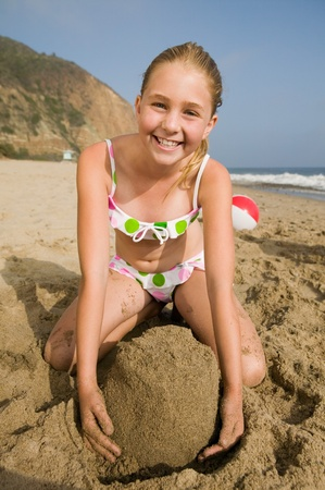 children sandcastle: Girl Playing in Sand at Beach
