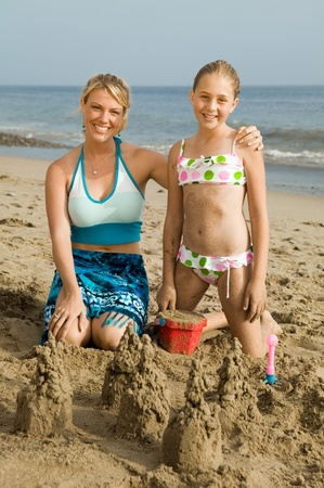 children sandcastle: Mother and Young Daughter Building Sand Castle on Beach