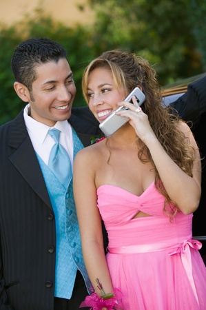 Well-dressed young couple using cell phone outside Stock Photo - 8836152