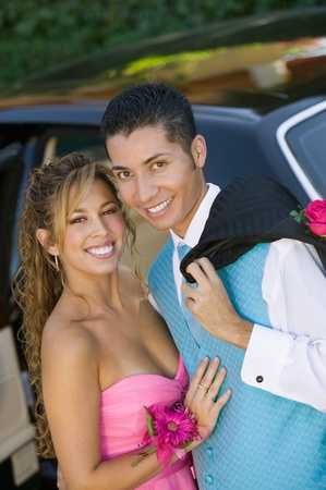 prom: Well dressed teenage couple outside limo portrait