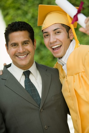 graduation suit: Graduate hoisting diploma with arm around father outside portrait LANG_EVOIMAGES