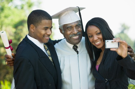 Senior graduate taking picture with grandchildren outside Stock Photo - 8836203