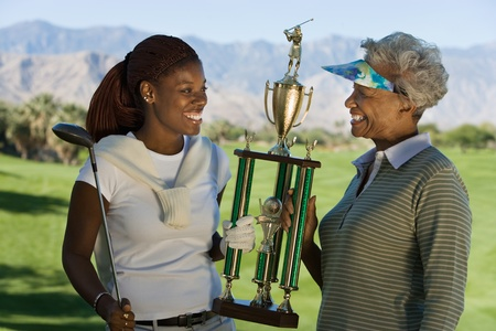 Grandmother and granddaughter holding golf trophy smiling Stock Photo - 8836278