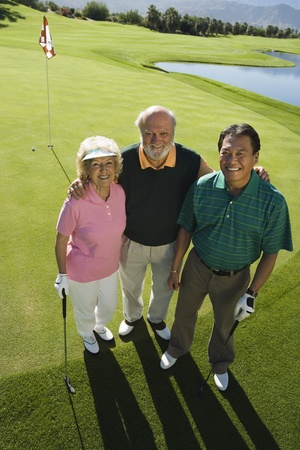 Senior couple with instructor on golf course smiling (portrait) (elevated view) Stock Photo - 8836283