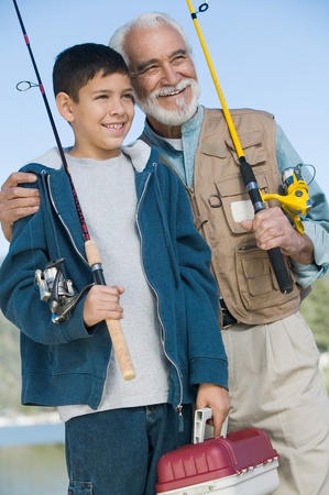 pre teen boys: Grandfather and grandson holding fishing rods outdoors smiling