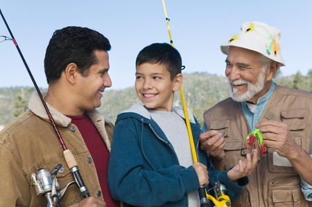 Male members of three generation family on fishing trip smiling Stock Photo - 8836303