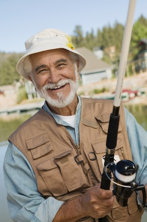 the ageing process: Middle-aged man fishing smiling (portrait)