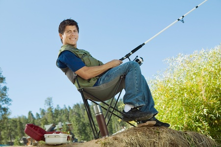 collapsible: Man fly fishing sitting on  collapsible chair (portrait)