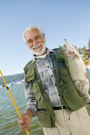 Middle-aged man holding up trout smiling (portrait) Stock Photo - 8836321