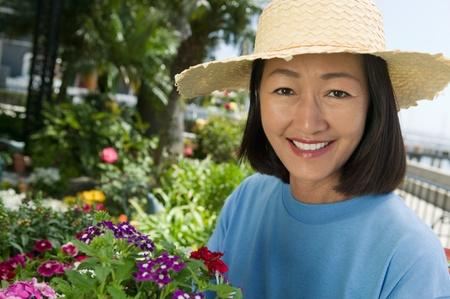 Woman in straw hat gardening (portrait)
