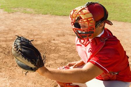 baseball diamond: Baseball catcher crouching on baseball field