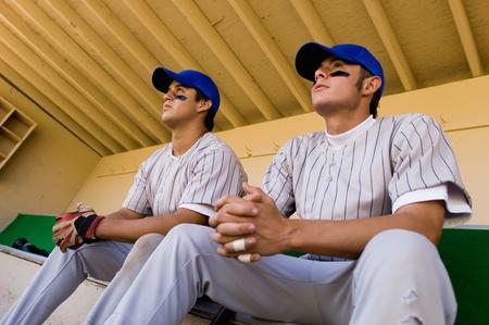 baseball dugout: Dos b�isbol compa�eros sentado en el dugout (vista de �ngulo bajo)