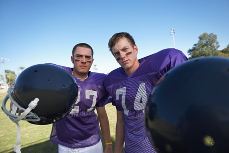 Two Football Players Holding Helmets on field portrait Stock Photo - 8836448