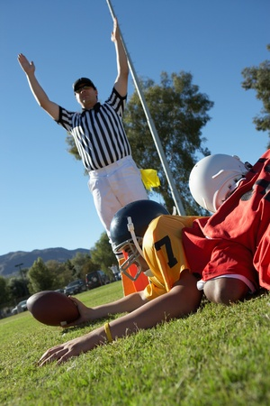signalling: Referee signalling touchdown over football player tackled in end zone