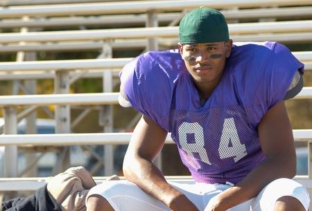 bleachers: Football player sitting on bleachers LANG_EVOIMAGES