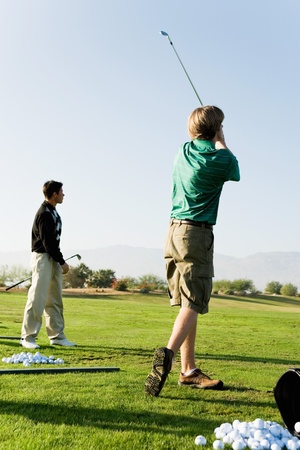 Two man practising at golf course Stock Photo - 8836462