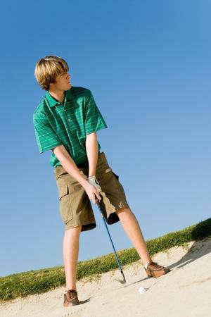 legs apart: Golfista golpear la bola de la trampa de arena LANG_EVOIMAGES