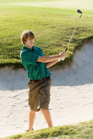 Golfer hitting ball from sand trap Stock Photo - 8836497
