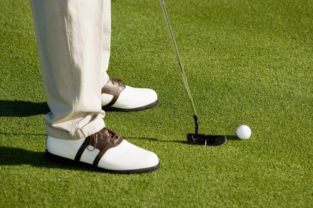 Golfer putting on green (low section) Stock Photo - 8836500