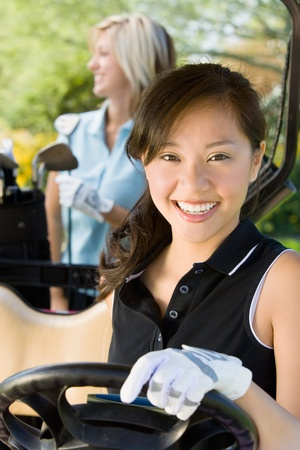 one person with others: Female golfer sitting in golf cart