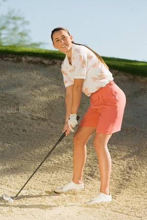 jambes �cart�es: Golfeuse frapper la balle du pi�ge de sable