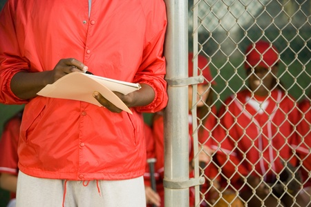 Softball coach writing on paper mid section Stock Photo - 8836529