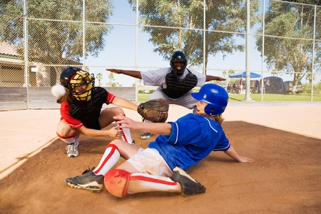 an umpire: Softball player slideing into home plate LANG_EVOIMAGES
