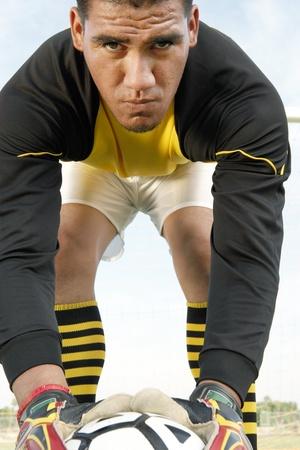 bending down: Portero plegado hacia abajo con el retrato de pelota