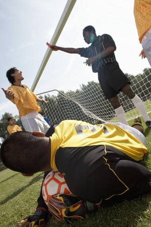 Goalkeeper on ground holding soccer ball while referee gives red card Stock Photo - 8822520