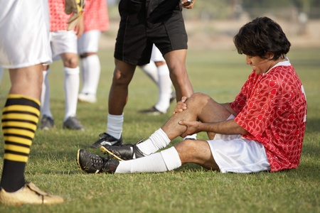 Injured soccer player sitting on pitch portrait Stock Photo - 8836558