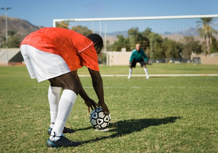Soccer player preparing for penalty kick back view