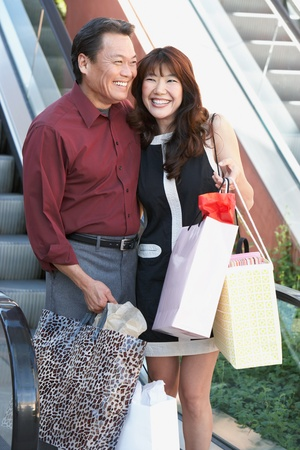 shopping trip: Smiling Couple standing side by side near escalator hugging on Shopping Trip