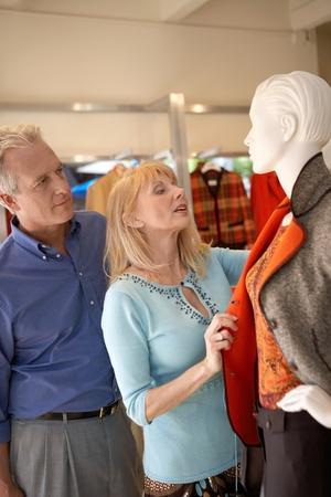 shopping trip: Couple looking at coat on Mannequin in clothing store on Shopping Trip